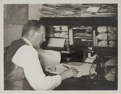 Photograph: Portrait: W. Hampton-Reynolds (Writing Specialists) seated at desk (Waiouru?)