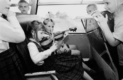 Entertaining Her Friends On The School Bus, Seven-Year-Old Julia Lissington Practises Her Violin On The Way Home